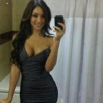 Sexy brunette taking selfie in revealing dress