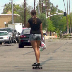 Teen girl in denim shorts on skateboard