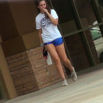 Cute athletic college girl in blue shorts
